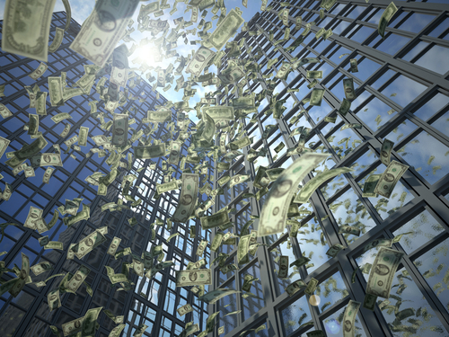 Money is cascading from the top of a skyscraper, representing the way a nonprofit board of directors can lose money by seeking leadership from the business world.