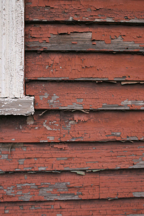 Peeling red paint on a slat wall.