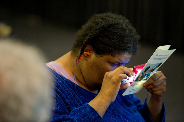 A person with a disability uses a magnifier to read a pamphlet.