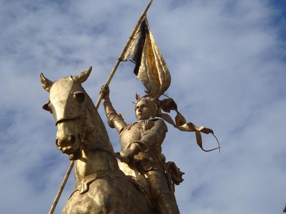 statue of a women riding a horse holding a flag