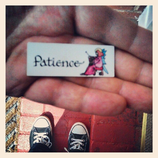 "A hand holds a small piece of paper with a seated female figure and the word ""Patience"" in calligraphy. It's a call for thoughtful action, as in the case of patient philanthropy."