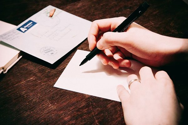 a right handed person, holding a black pen against a white paper. Picture used in an article about how some foundation presidents are defending donor advised funds.