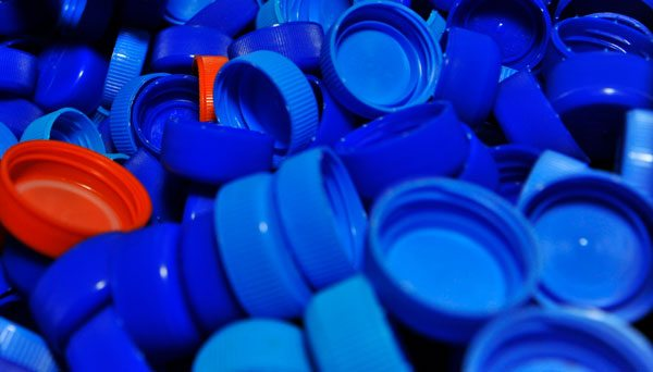 bottle caps all in blue except for two which are in red. Image used for article about google's ad grants