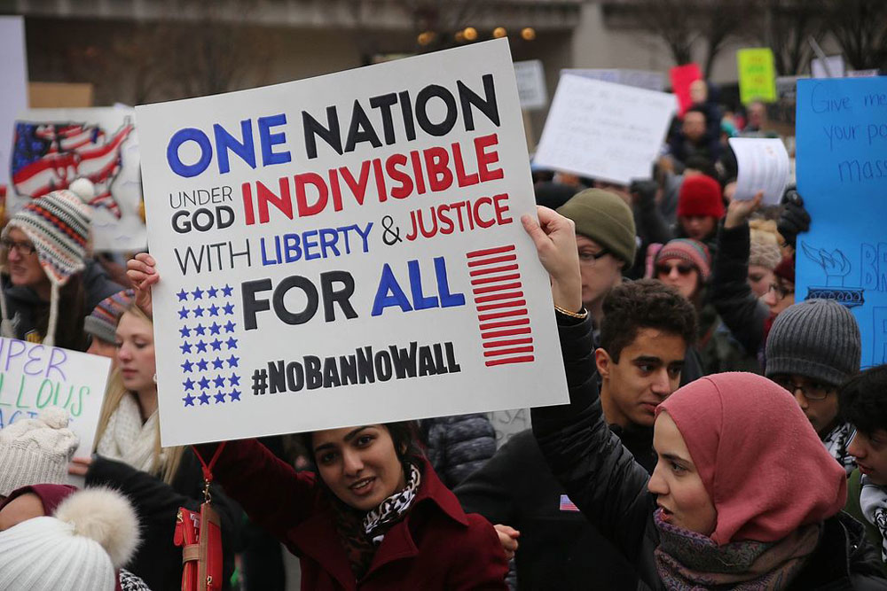 "Women holding a poster reading ""One Nation under God Indivisible with Liberty and Justice for All #NoBanNoWall"""