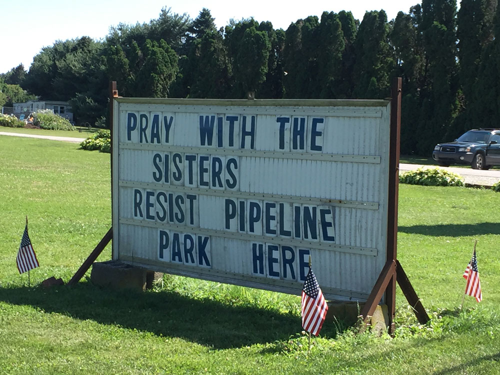 "A sign reading, ""Pray with the Sisters. Resist Pipeline. Park Here."""