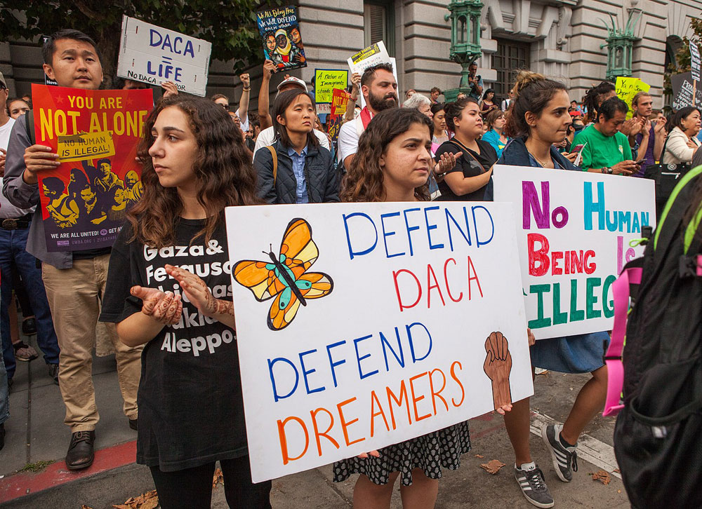Protesters holding signs in defense of DACA and the Dreamers.