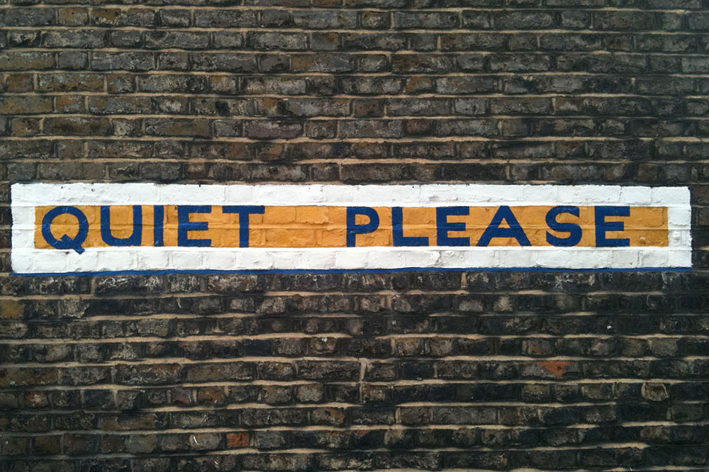 "A painted sign reading, ""Quiet Please."""