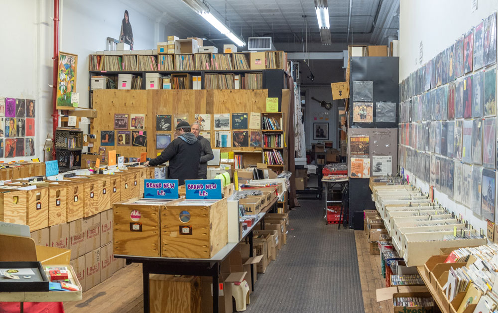 Archive of Contemporary Music in New York City. A man looking through a crate of records in a room filled with them. Vinyl album sleeves cover the walls.