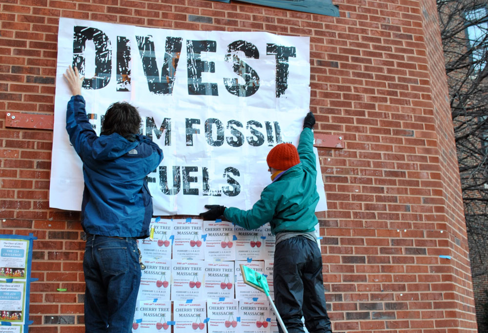 "Two students hang a poster that reads ""Divest from Fossil Fuels"" on a brick wall."