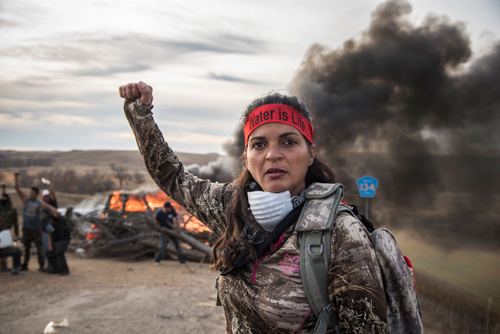 "Photo shows: a Field Medic wearing camo and a red headband that reads: ""Water is Life,"" raising her right fist. A large wood fire behind her blocks a road. Fellow Water Protectors behind her also have fists raised."