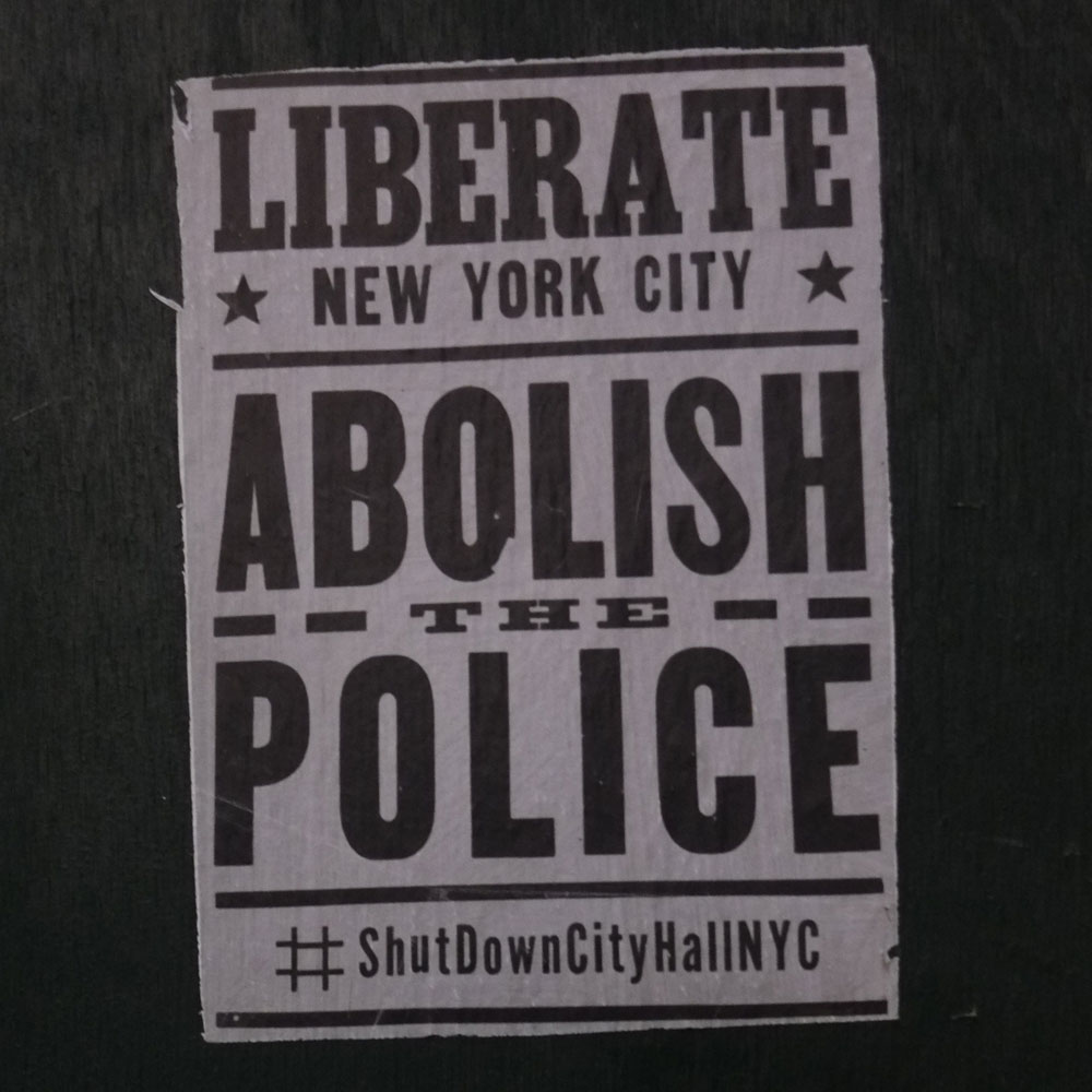 "A poster that reads ""Liberate New York City – Abolish the Police – #ShutDownCityHallNYC"""
