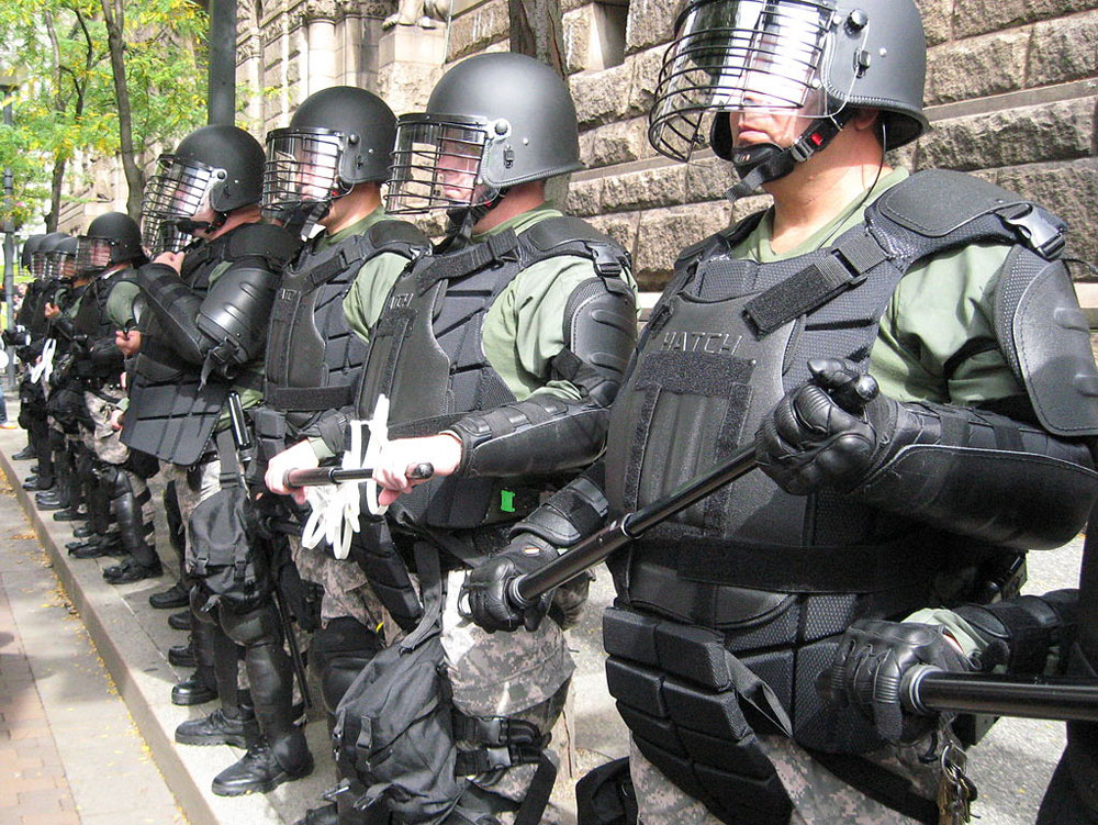 Pittsburgh police officers in helmets and heavy body armor, holding truncheons.